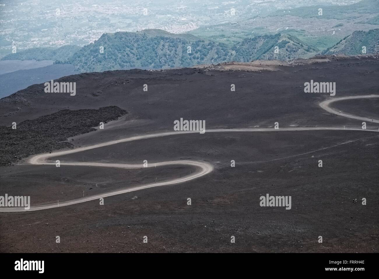 Italy, Sicily, Mt Etna: Volcanic landscape with winding dusty road - Stock Image