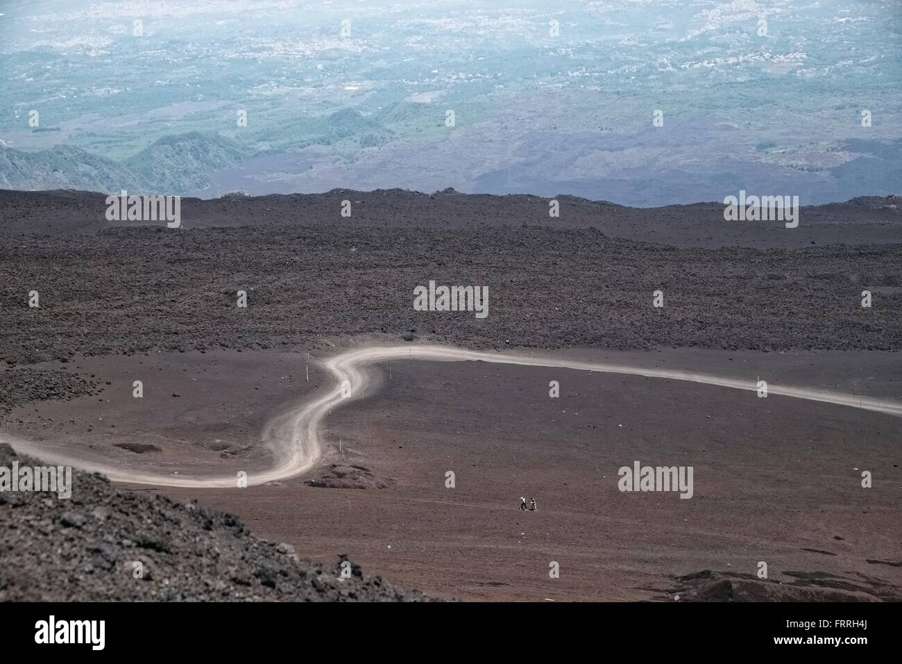 Italy, Sicily, Mt Etna: Volcanic landscape with winding dusty road with sea in distance - Stock Image