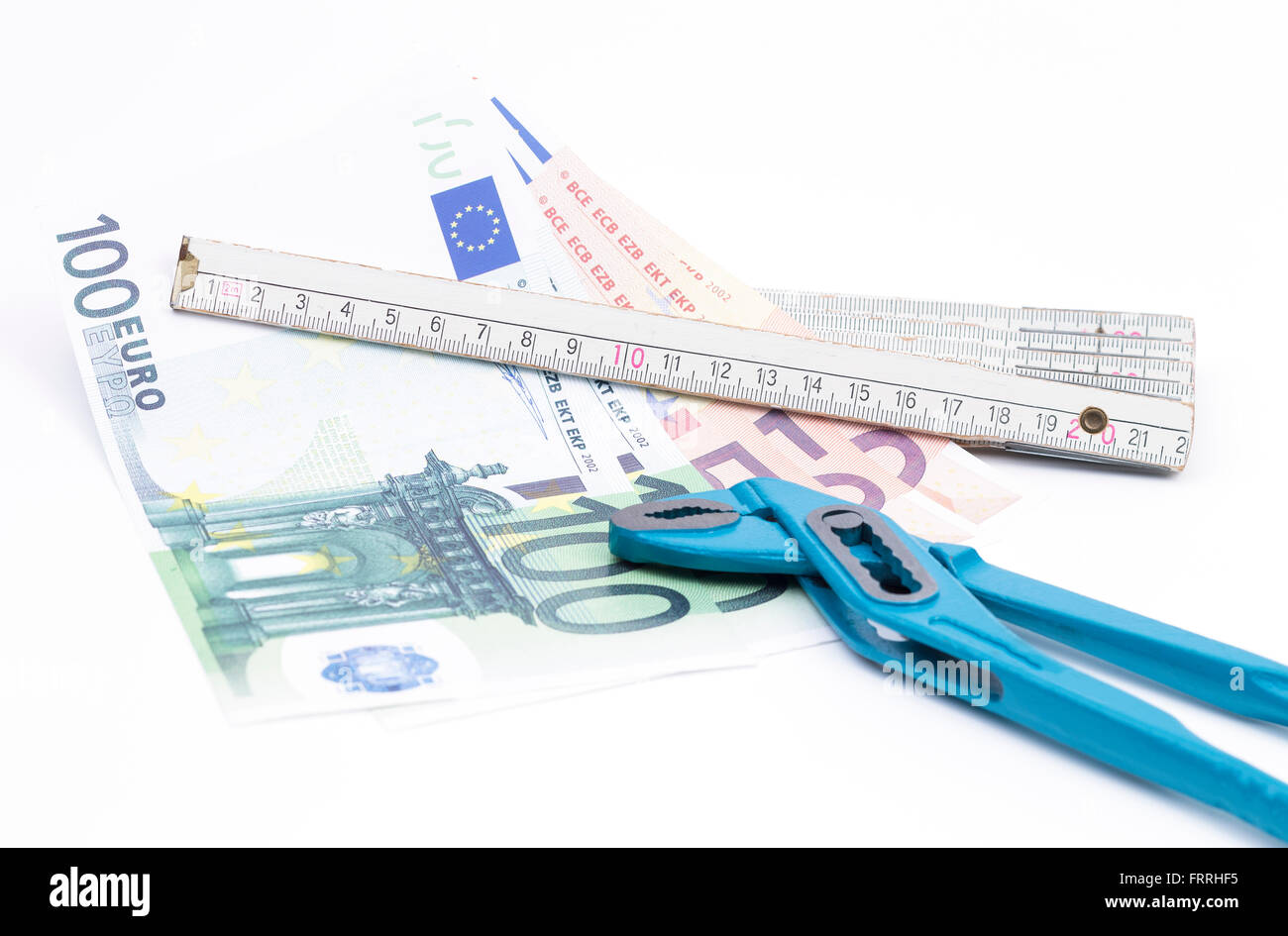 Image shows a yardstick with money and pliers isolated on white - Stock Image