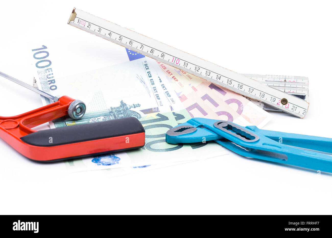 Image shows a yardstick with money and tools isolated on white - Stock Image
