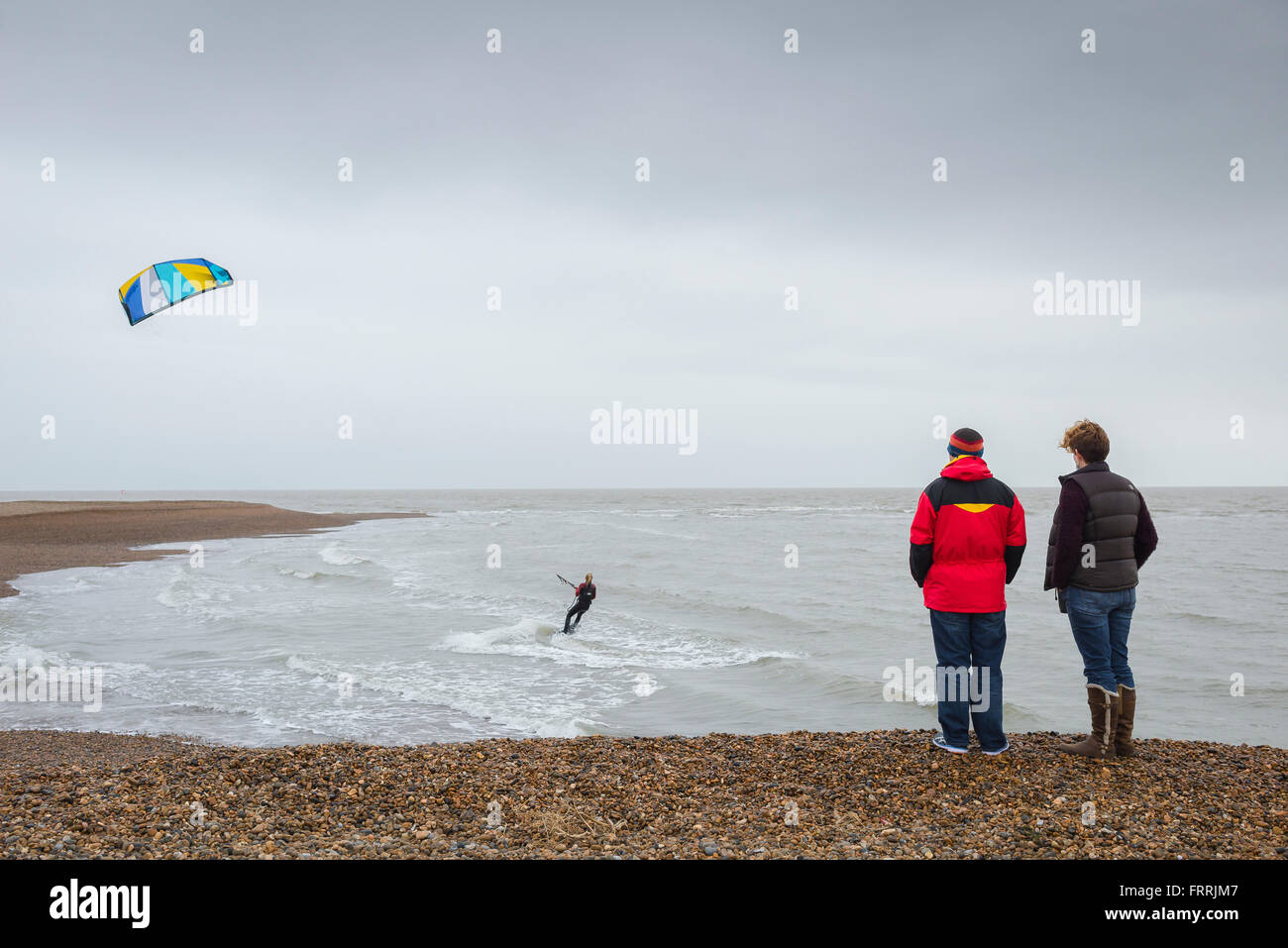 People watching kite surfing, rear view of a couple standing on Hollesley Beach on the Suffolk coast,England,watching Stock Photo