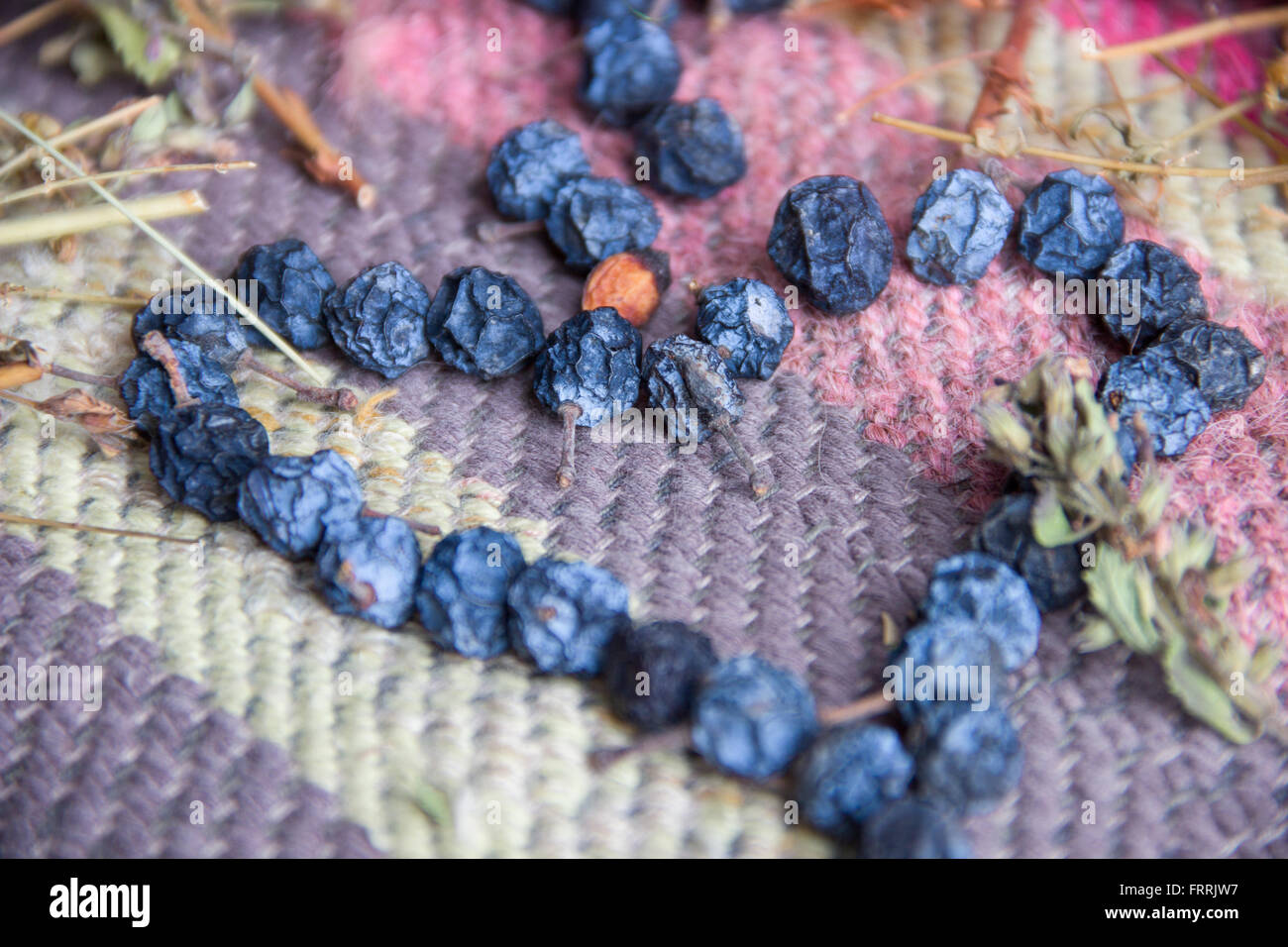 Dried blue berries on colorful ethnic in shape of heart. - Stock Image