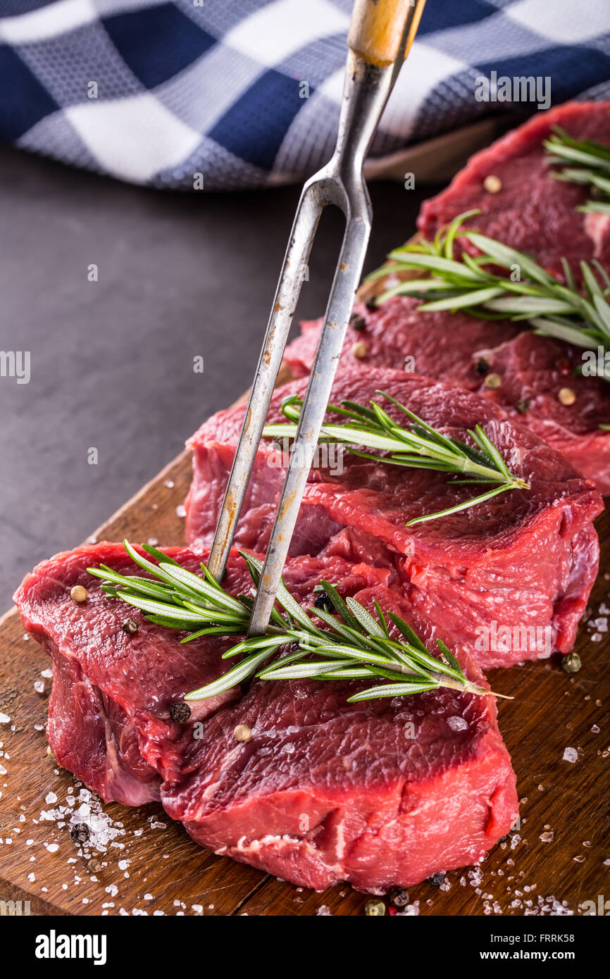 Steak. Raw beef steak. Fresh raw Sirloin beef steak sliced or whole ready for BBQ or grill. Herb - Rosemary decoration. - Stock Image