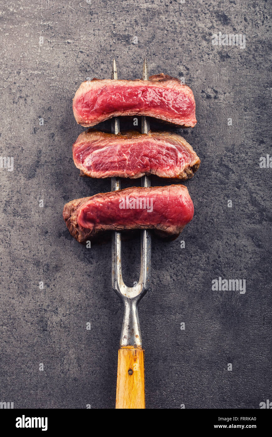 Steak. Grill beef steak. Slices of sirloin beef steak on meat fork on concrete background. - Stock Image