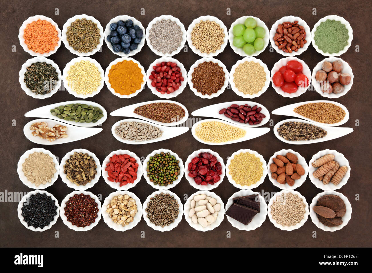 Health and diet super food selection in porcelain dishes over lokta paper background. High in vitamins and antioxidants. - Stock Image