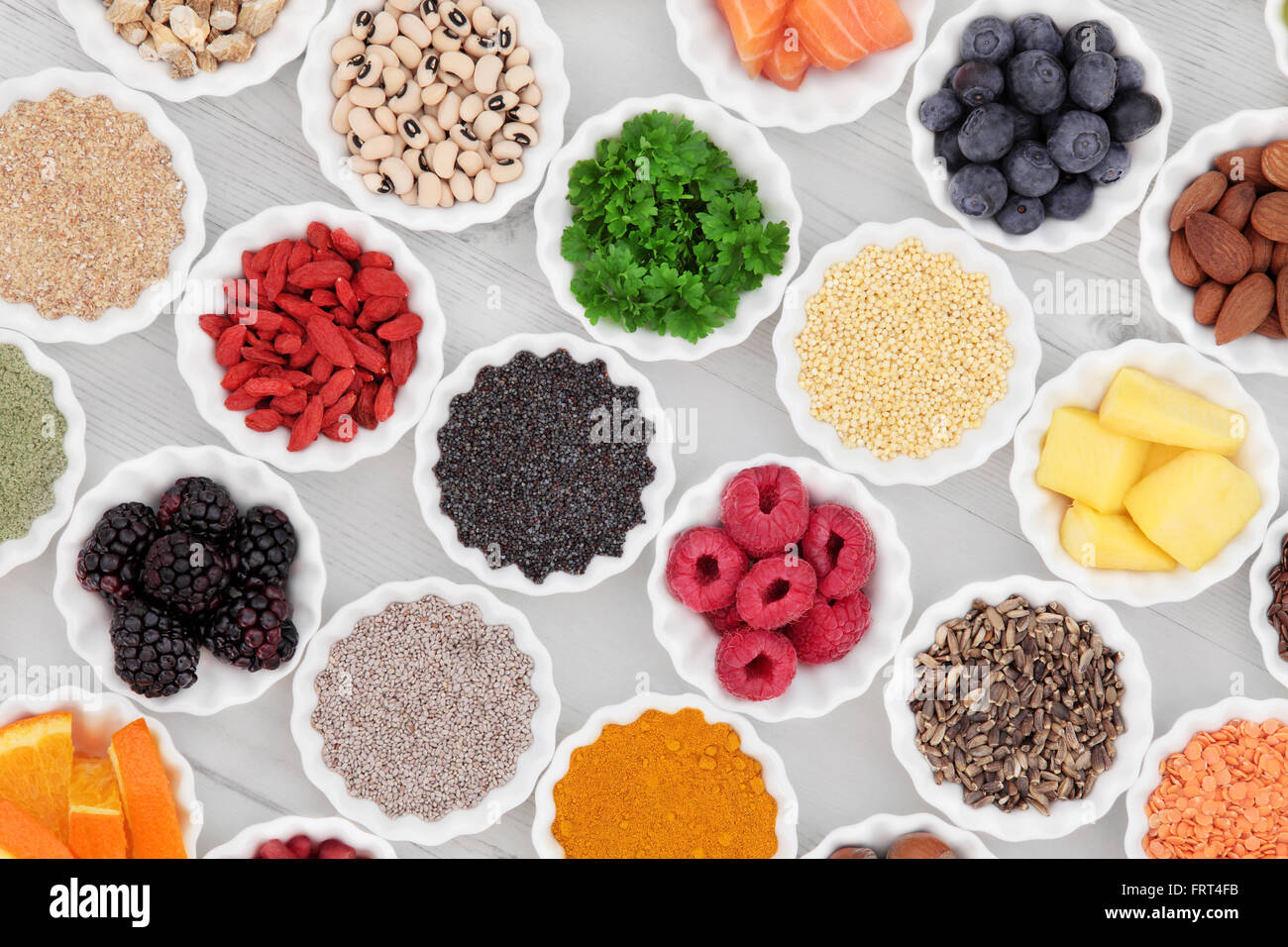 Super food collection in porcelain crinkle bowls over distressed wooden background. High in vitamins and antioxidants. - Stock Image