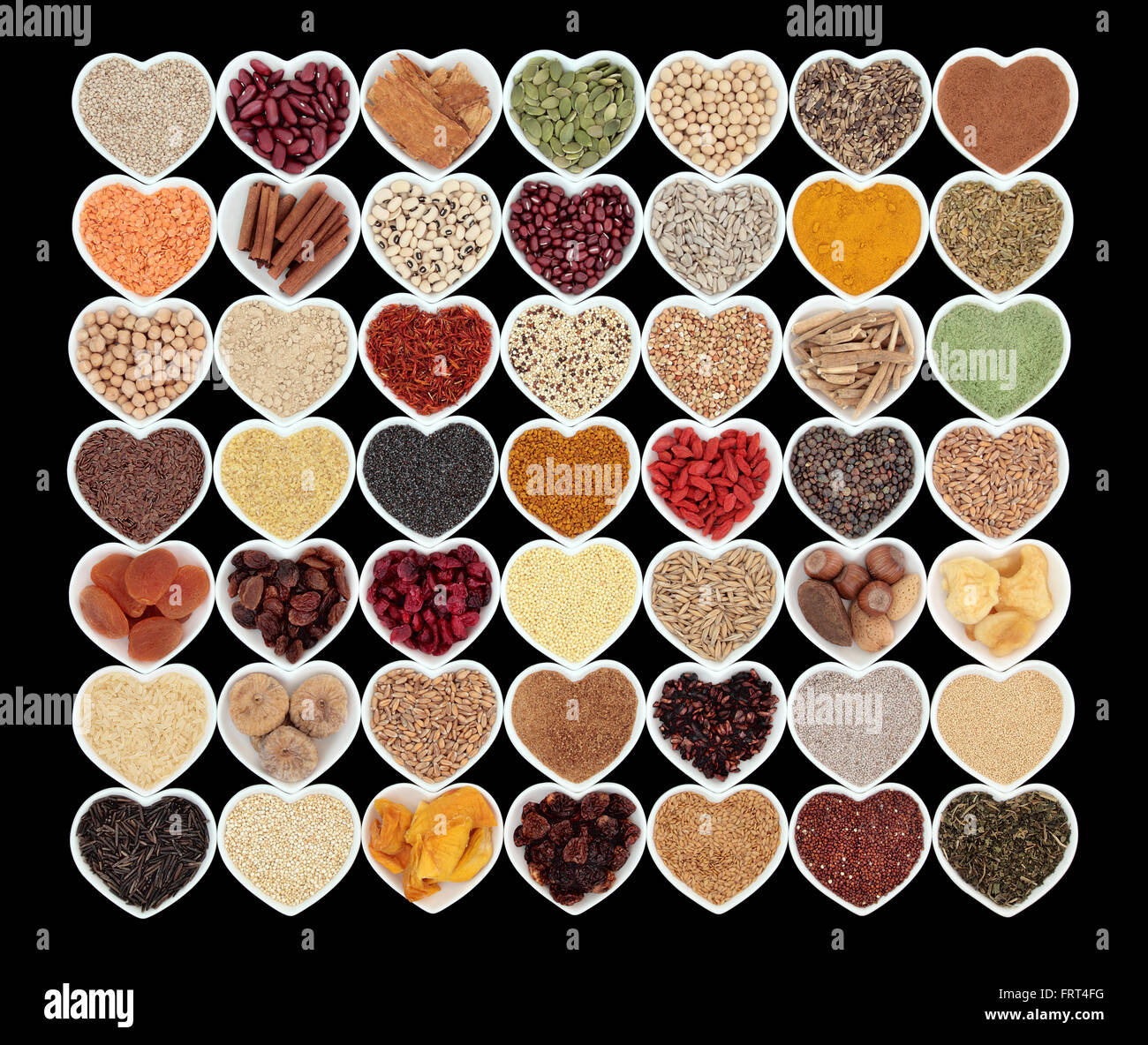 Large healthy dried super food in heart shaped bowls over black background. High in antioxidants, minerals and vitamins. - Stock Image