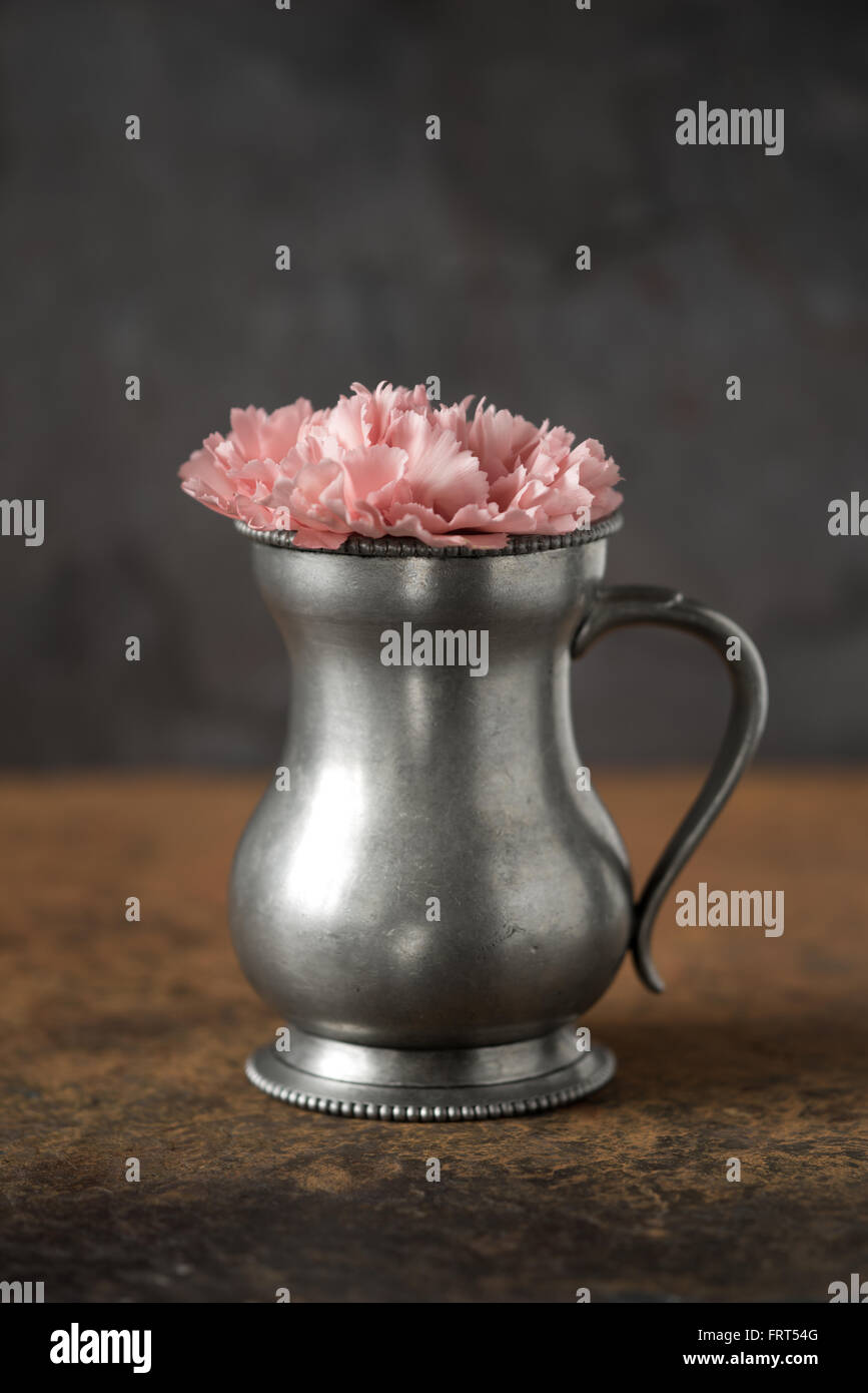 Carnation in the metal vase on the stone table vertical - Stock Image