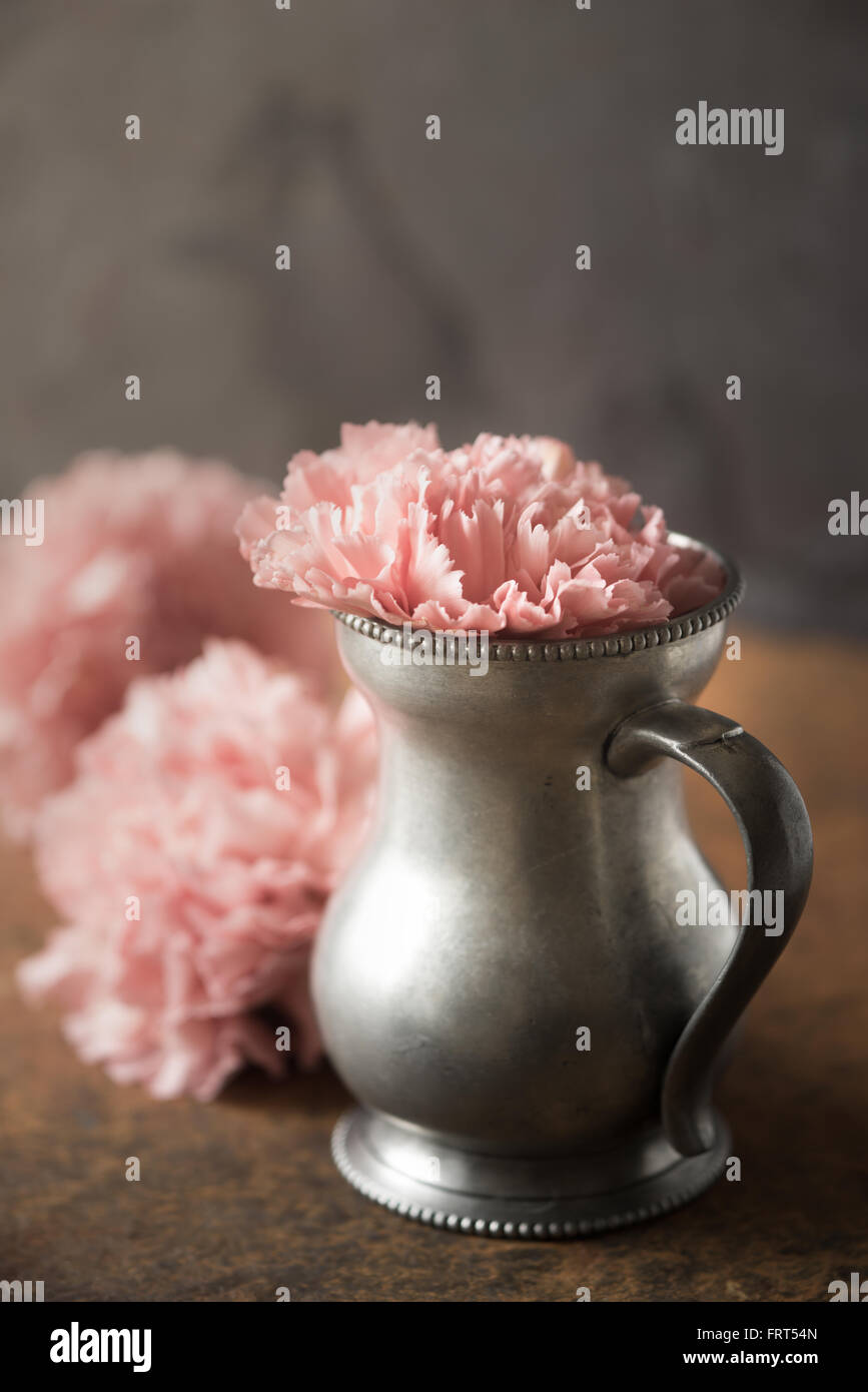 Carnation in the metal vase on the stone table - Stock Image
