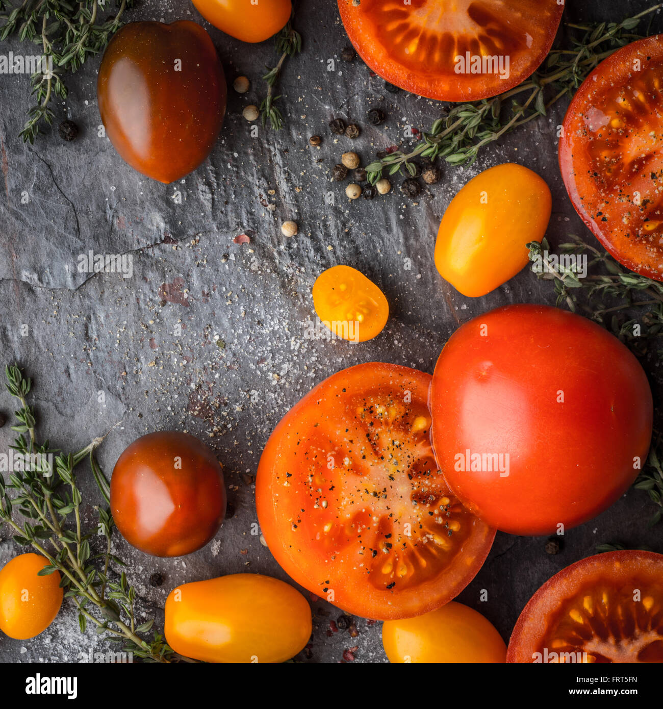 Tomatoes mix  with herbs on the stone table square - Stock Image