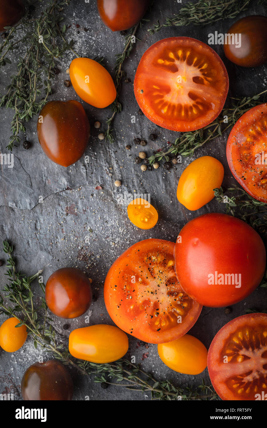 Tomatoes mix  with herbs on the stone table vertical - Stock Image