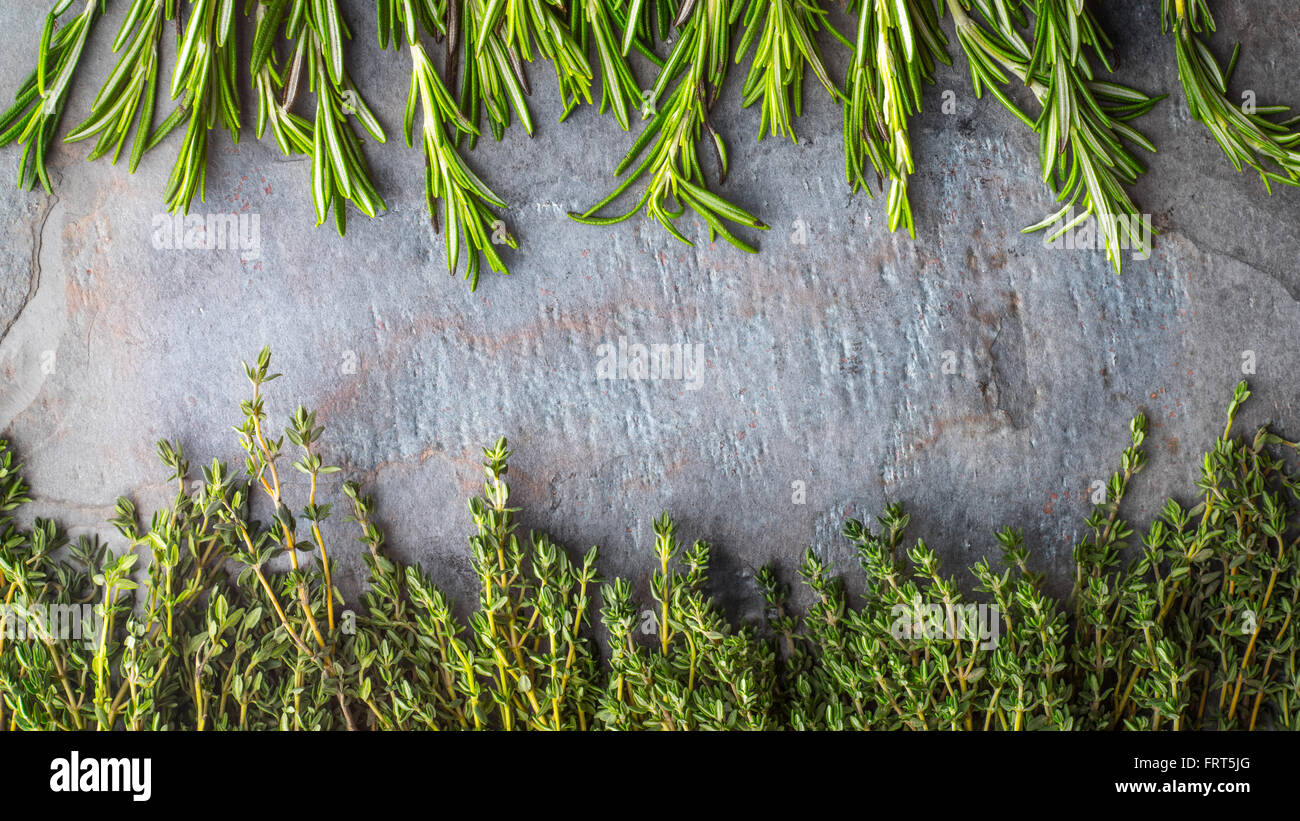 Thyme  and rosemary sprigs on the stone table - Stock Image