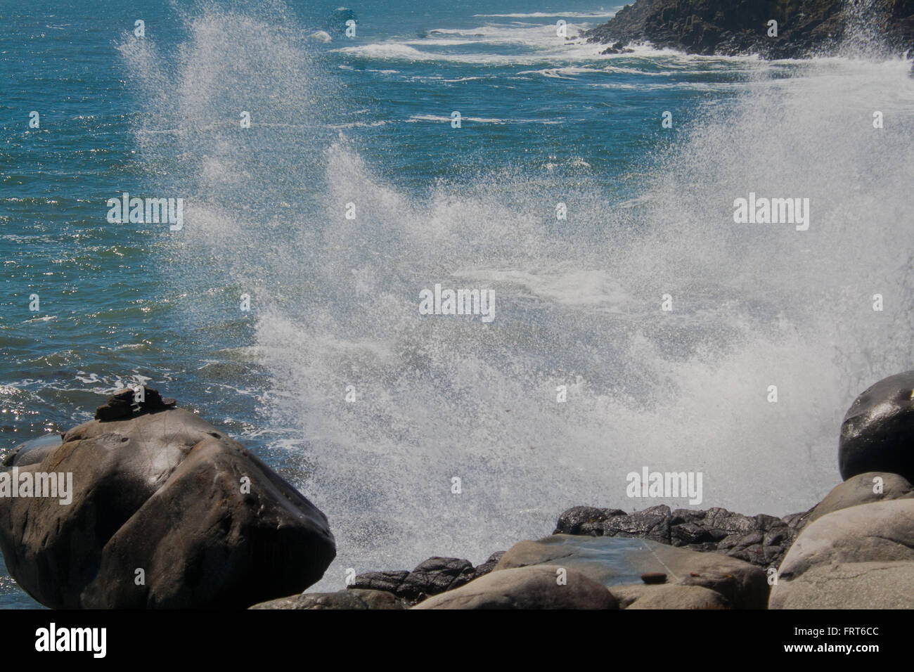 Forces of nature. The splash from a wave crashing the rocks below a cliff. - Stock Image