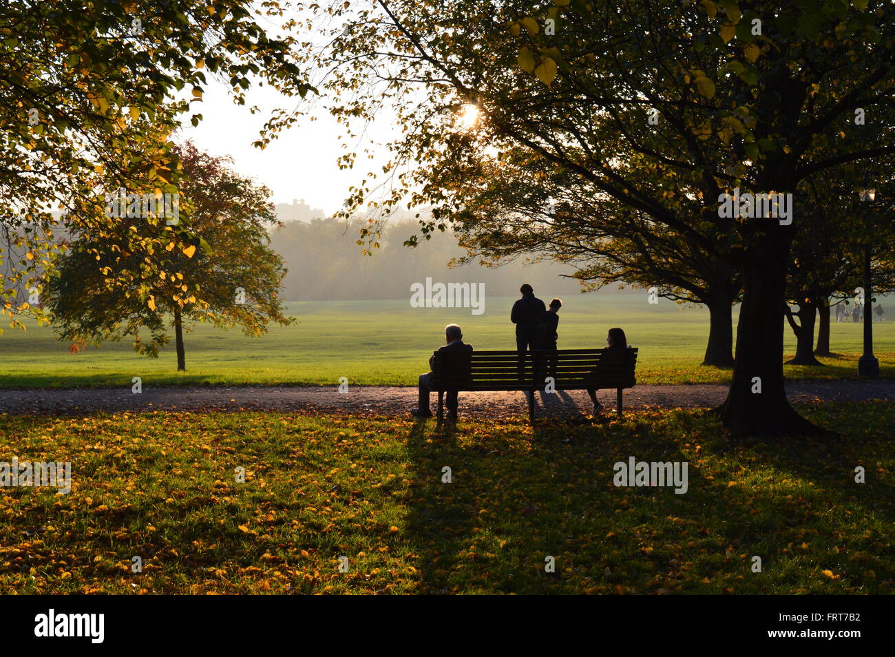 People enjoying the late afternoon sun in London's Primrose Hill Park Stock Photo
