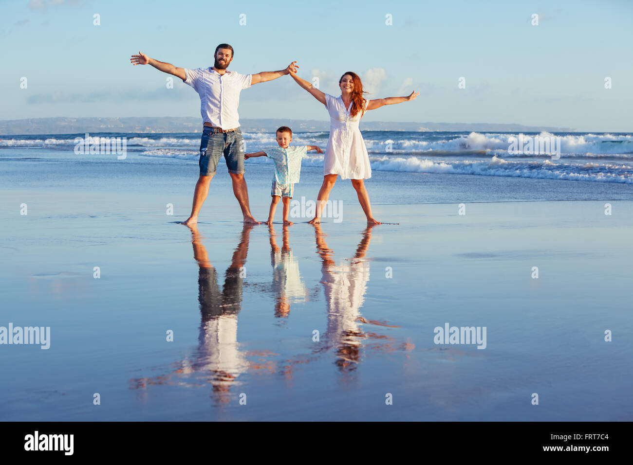 Happy family - father, mother, baby son walk with fun along edge of sunset sea surf on black sand beach. - Stock Image