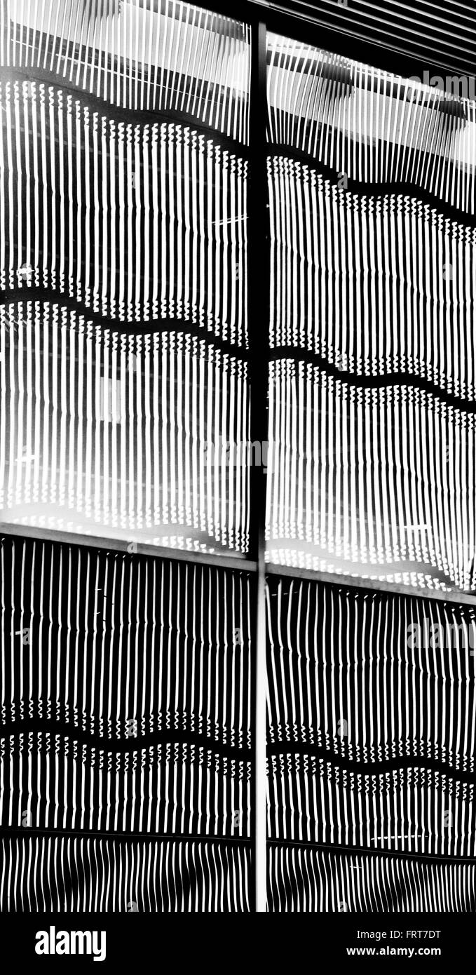 Wavy steelwork architecture on a multi Story car park reflected in glass windows abstract. Milton Keynes, Buckinghamshire, - Stock Image