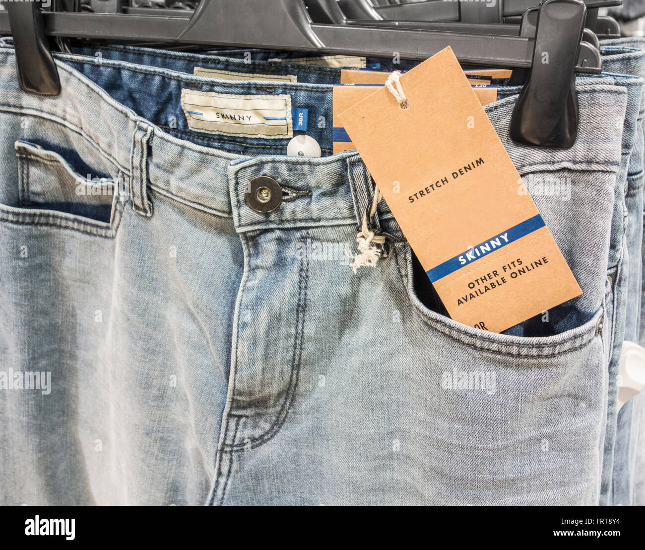 Skinny jeans in mens clothing store. UK - Stock Image