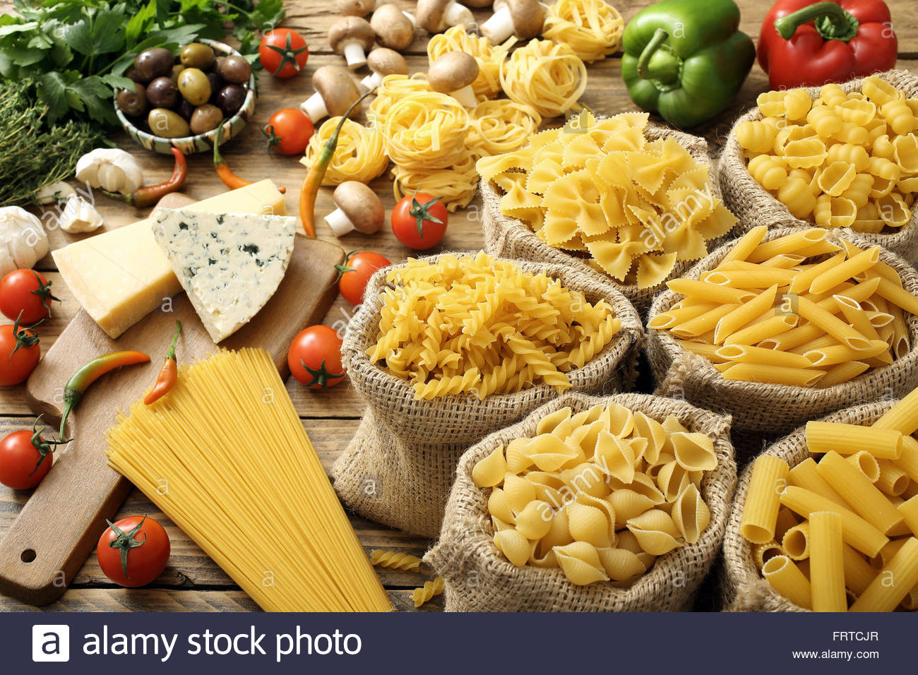 top view various types of Italian pasta with different ingredients on rustic background - Stock Image