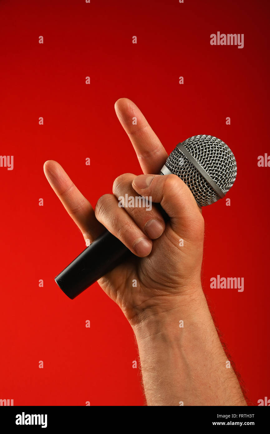 Man hand holding voice microphone with devil horns rock