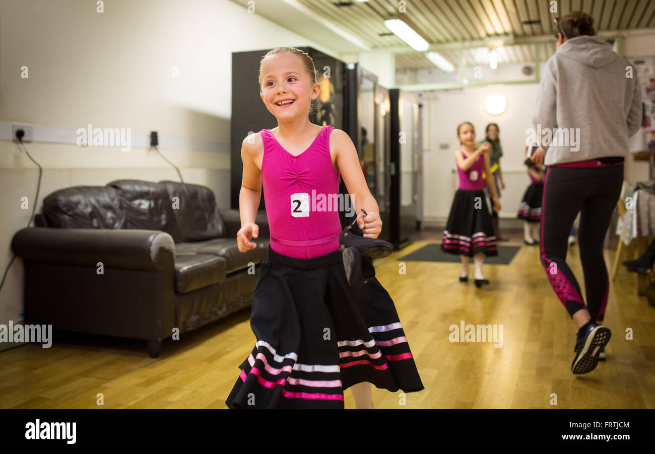 A young girl runs to meet her parents following her grade 1 ballet