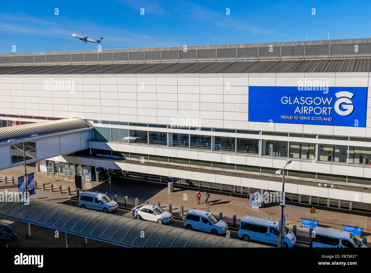 Terminal building of Glasgow Airport, Scotland, UK with taxi rank and planes in the background - Stock Image