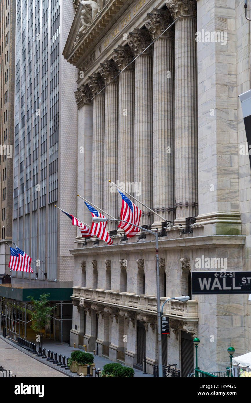 Wall street signpost with with New York Stock Exchange background, NYC, USA - Stock Image