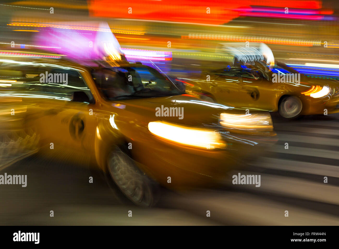Blurry abstract photo of yellow taxi cabs in motion in Manhattan, New York City - Stock Image