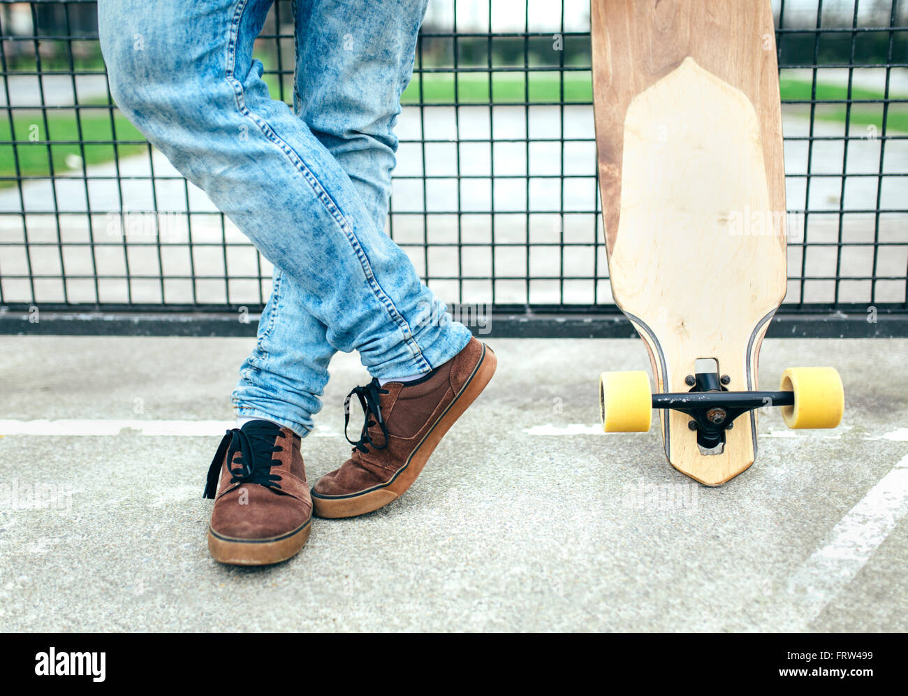Legs of young man besides skateboard - Stock Image
