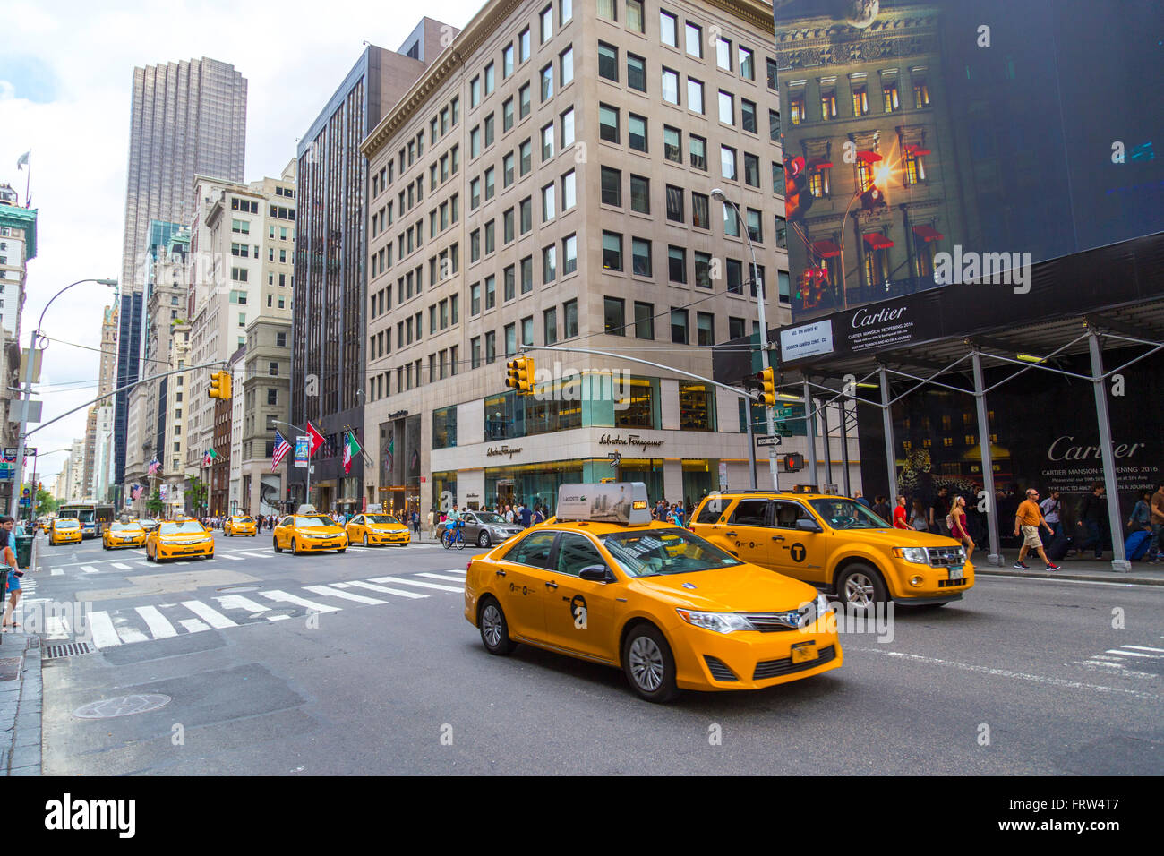 Yellow taxi cabs ride on 5th Avenue in New York City, USA. - Stock Image