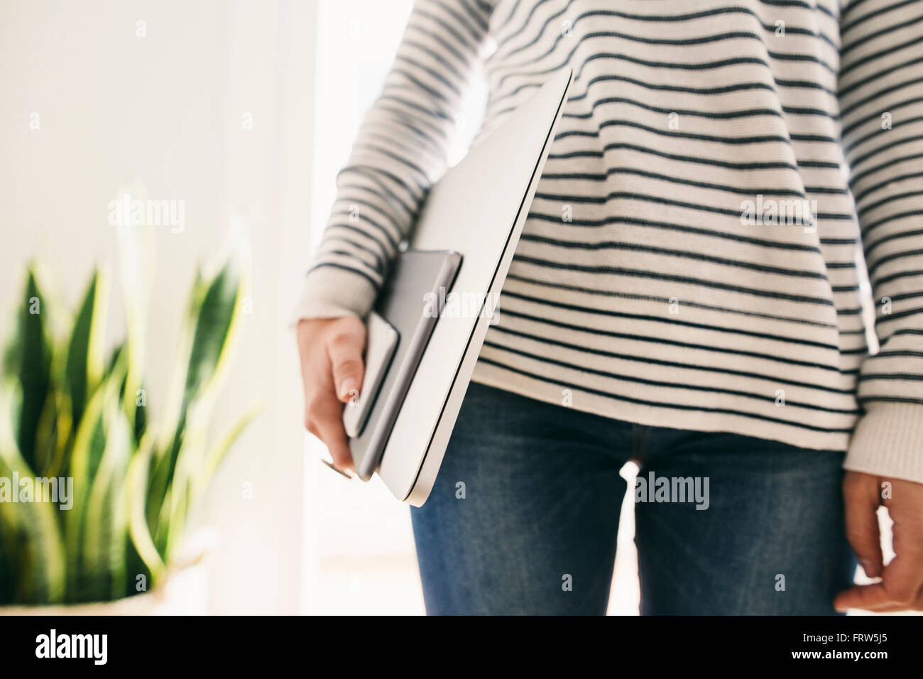 Woman holding portable devices in different sizes - Stock Image