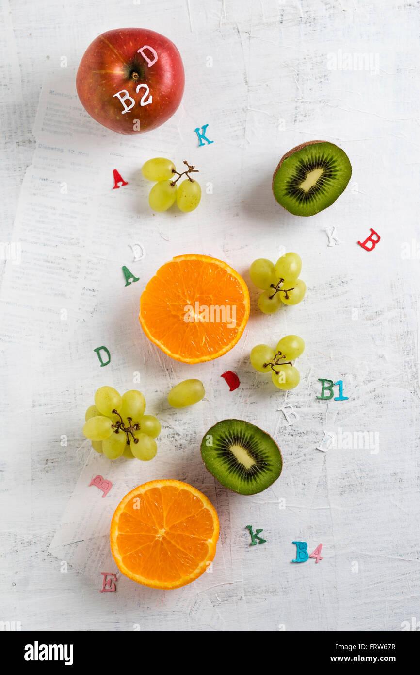 Banane, apple, orange, kiwi and green grapes, different vitamins - Stock Image