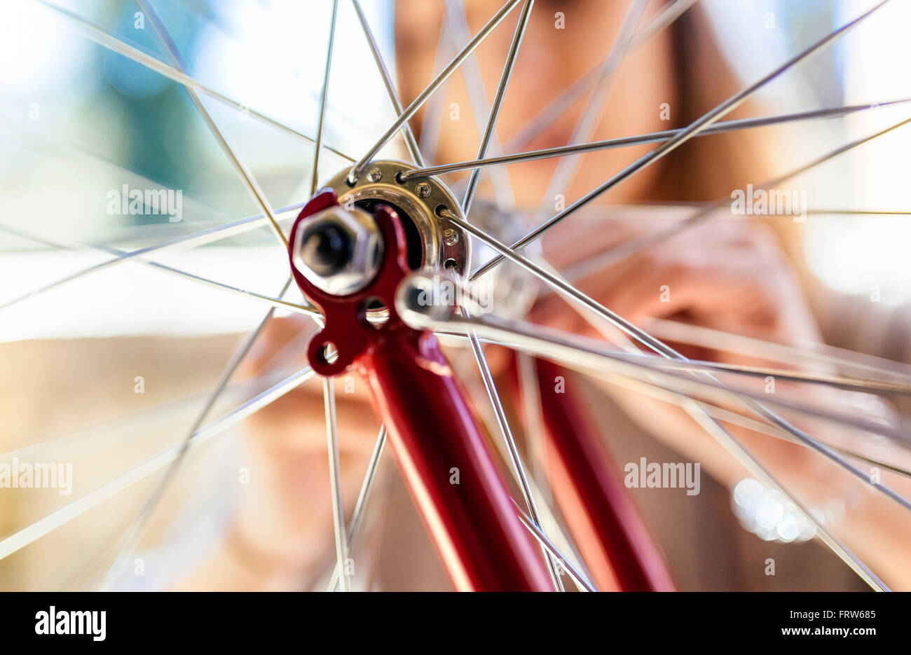 Young woman and detail of a bicycle tire - Stock Image