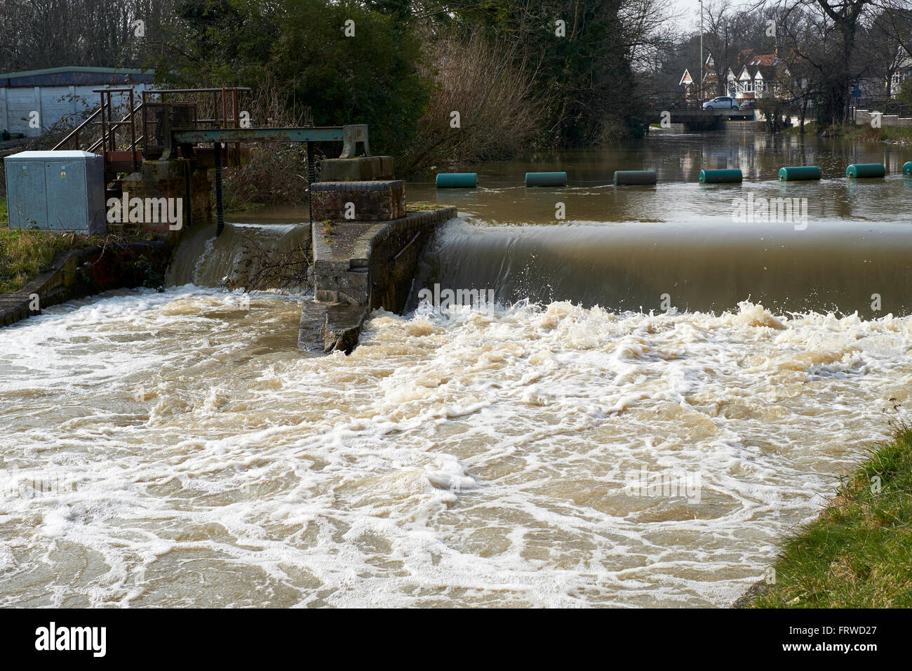 Floodwater flowing over a weir and gauging station on the River Great Ouse, Bedford, Bedfordshire, United Kingdom. Stock Photo