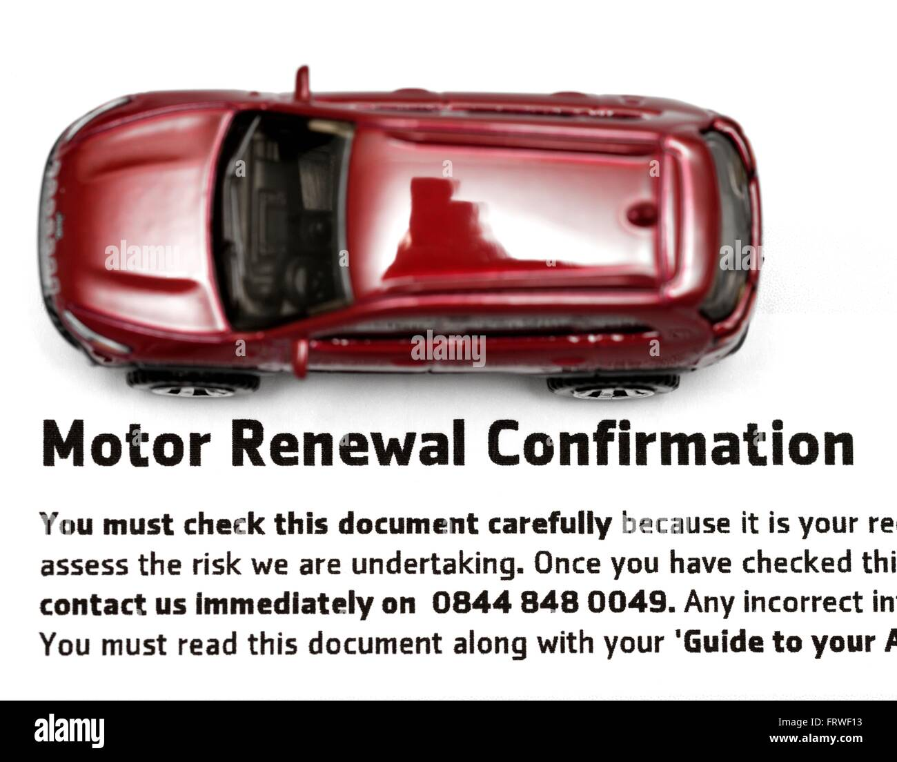 A miniature red car on a motor renewal confirmation document.. - Stock Image