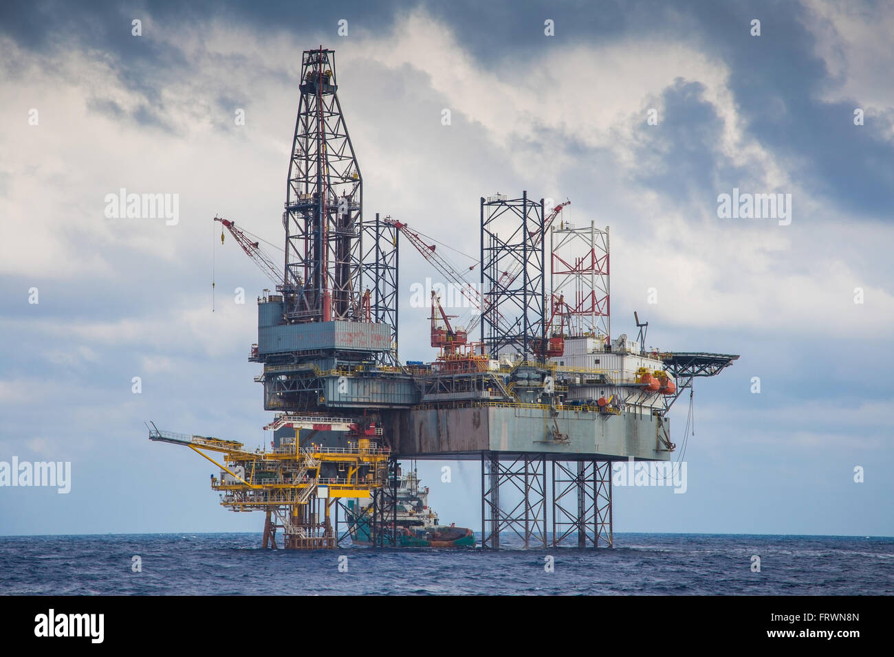 Oil and gas drilling rig work over remote wellhead platform to completion oil and gas produce well by using drilling - Stock Image
