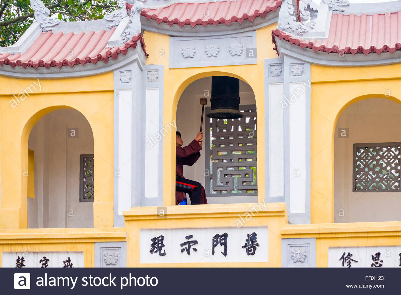 A novice monk rings a bell at One Pillar Pagoda temple complex, Hanoi, Vietnam - Stock Image