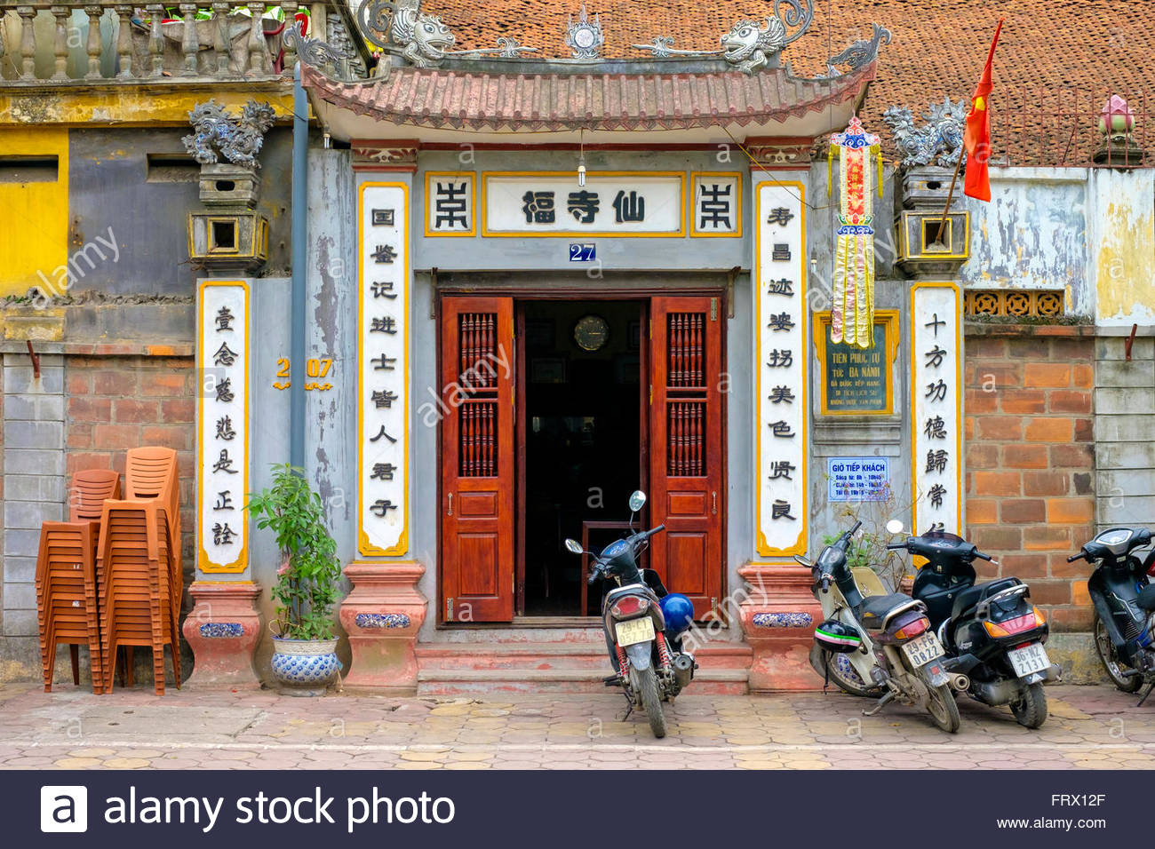 Motorbikes parked outside of small temple, Dong Da District, Hanoi, Vietnam - Stock Image