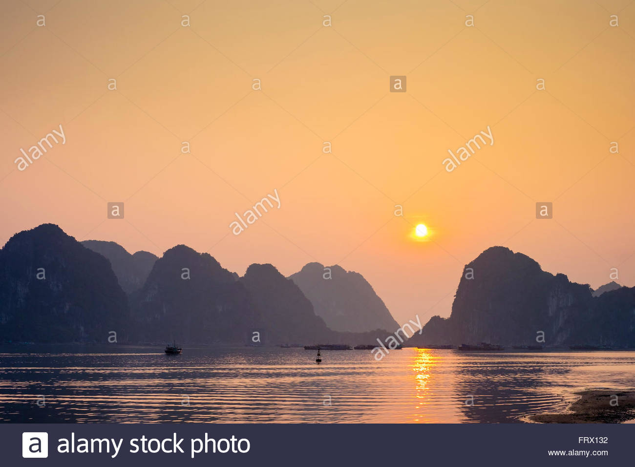 Sunset over karst mountains in Ha Long Bay, Quang Ninh Province, Vietnam Stock Photo