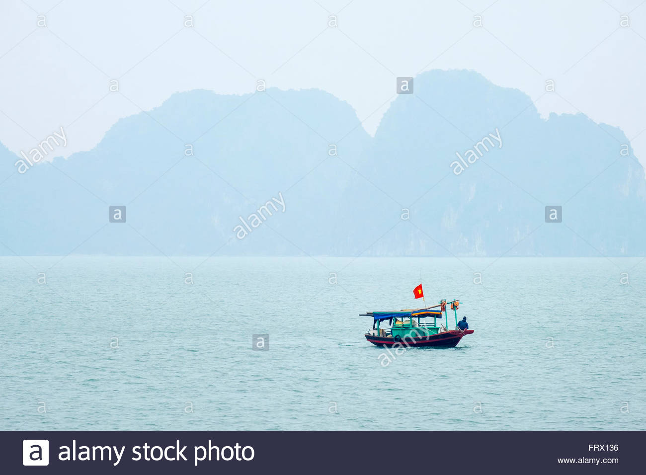 Small fishing boat in Ha Long bay on a foggy day, Quang Ninh Province, Vietnam - Stock Image