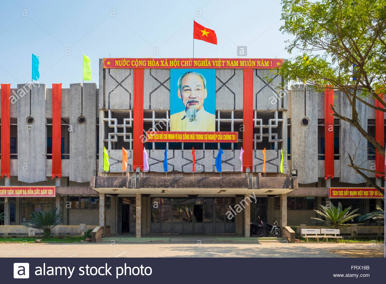 Portrait of Ho Chi Minh and Vietnamese flag on a government building, Nam Phuoc, Quang Nam Province, Vietnam - Stock Image