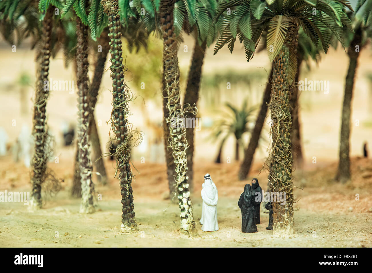 Little Figurines Of Arabs In The Desert Oasis Under The Palm Trees