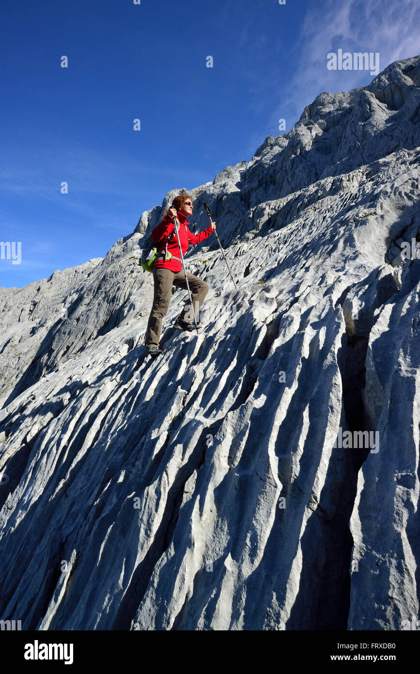 Woman ascending on limestone slab to Hoher Goell, Berchtesgaden National Park, Berchtesgaden Alps, Upper Bavaria, Stock Photo