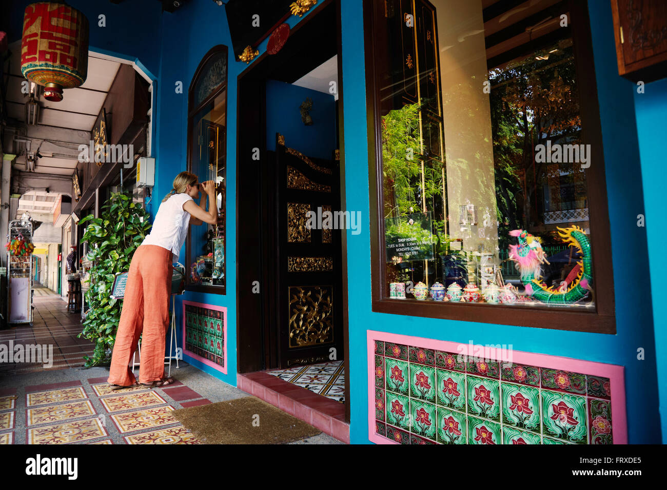 Woman looking throuhg a shopwindow of an antique shop, Chinatown, Singapore - Stock Image