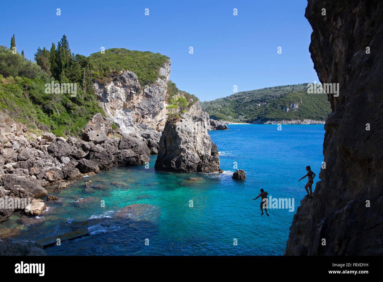 Man jumping from the cliff near the beach bar La Grotta, La Grotta Bay, near Paleokastritsa, Corfu island, Ionian - Stock Image