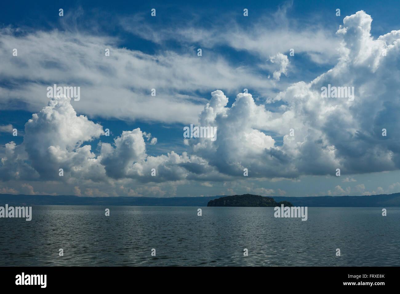 Cumulus clouds above lake Lago di Bolsena, Isola Martana im Hintergrund, crater lake of volcanic origin, near Montefiascone, - Stock Image