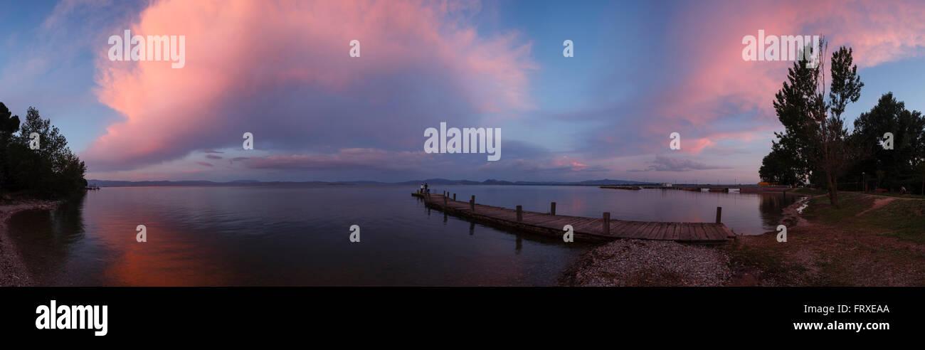 Jetty at the lake shore, clouds at sunset, Castiglione del Lago, Lago Trasimeno, province of Perugia, Umbria, Italy, - Stock Image