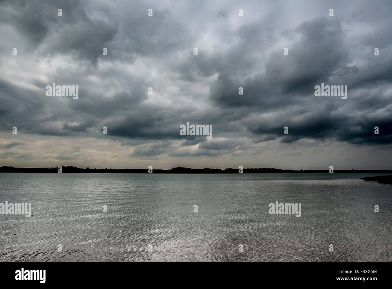 Highly reflective water on a cloudy morning - Stock Image
