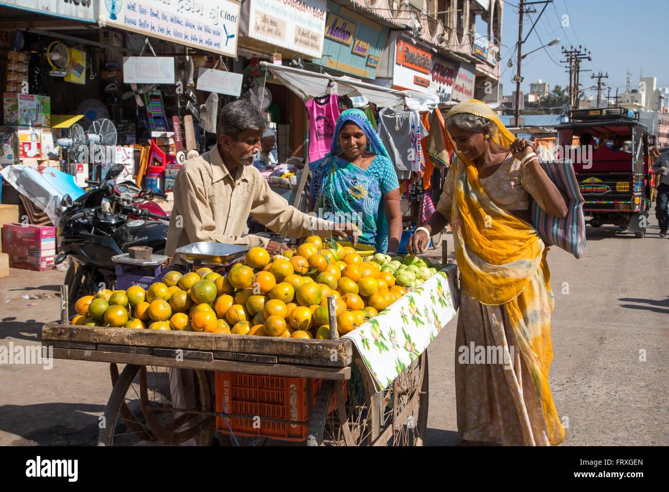 Two women at a fruit stand in the city center, Porbandar, Gujarat, India - Stock Image
