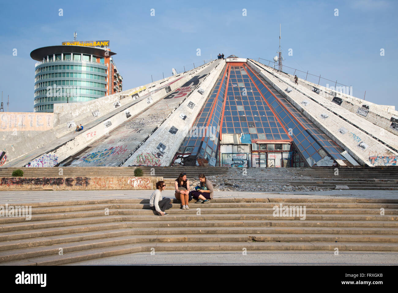 People sitting on the steps of the graffiti-covered The Pyramid International Center of Culture with glass high - Stock Image