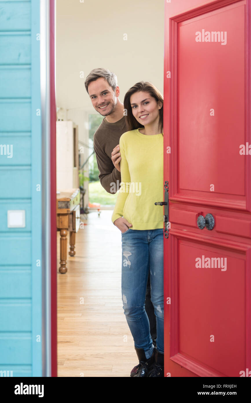 A grey hair man with beard and a woman are opening the red door of their house with wooden floor to welcome some - Stock Image